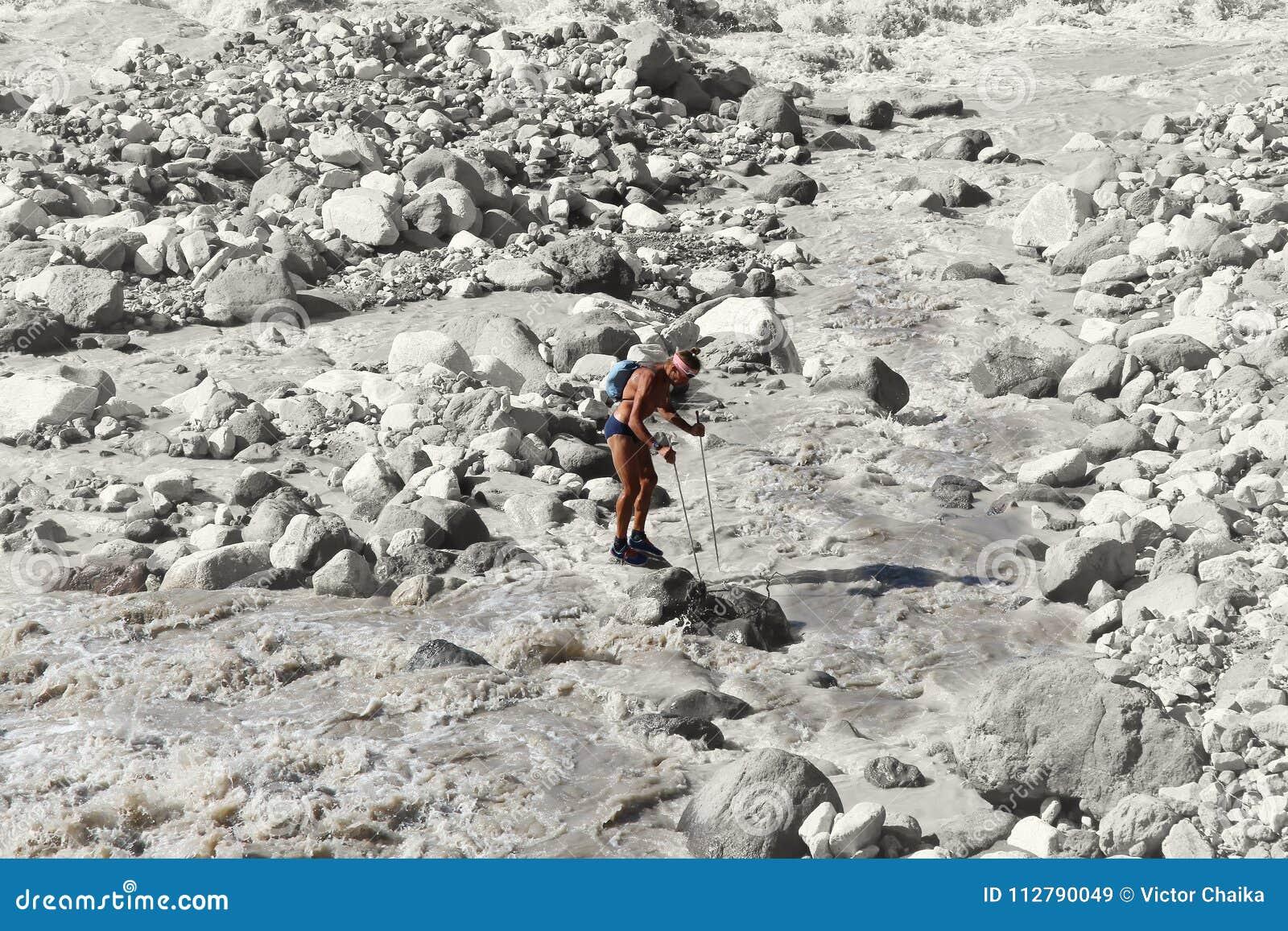Στάσεις οδοιπόρων σε έναν βράχο στη μέση ενός οργιμένος ποταμού βουνών