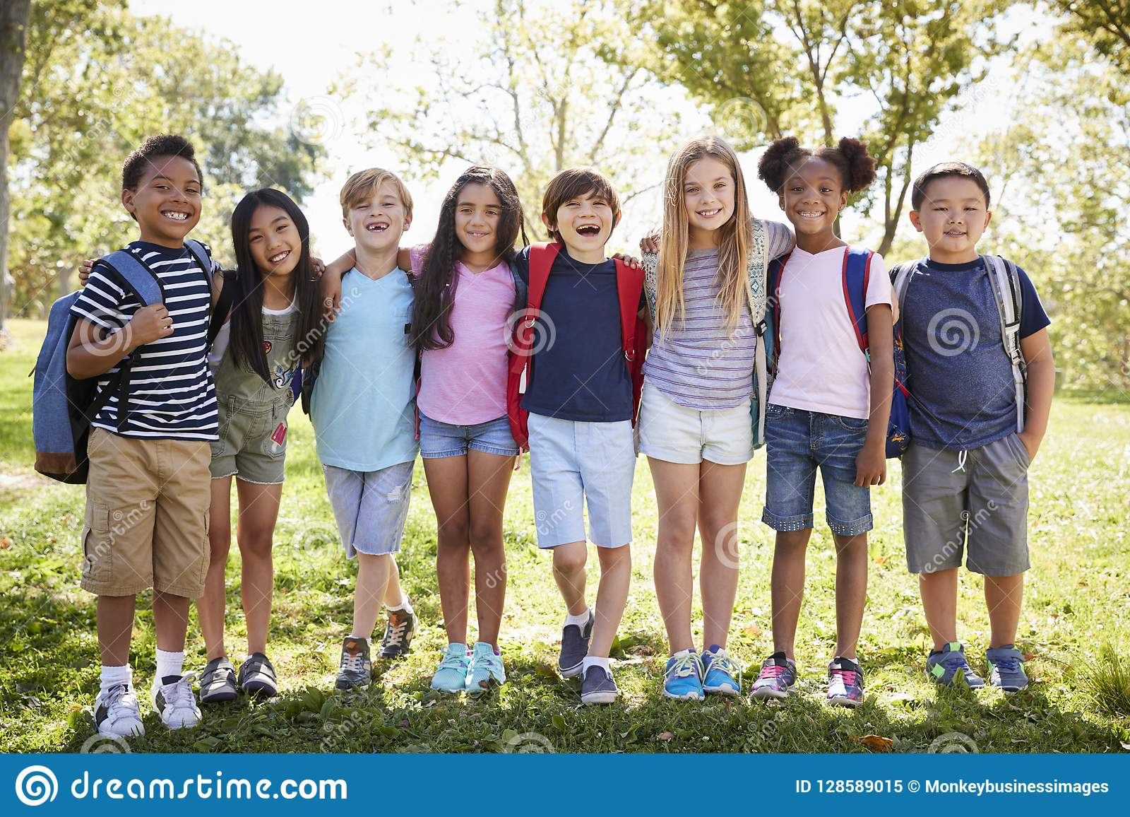 Στάση σχολικών παιδιών που αγκαλιάζει σε μια σειρά υπαίθρια, πλήρες μήκος
