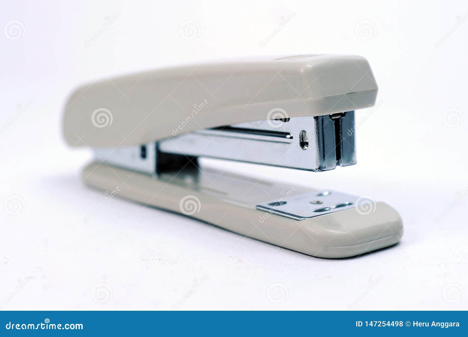 Στάσιμο γκρίζο stapler γραφείων με το σωρό των βάσεων