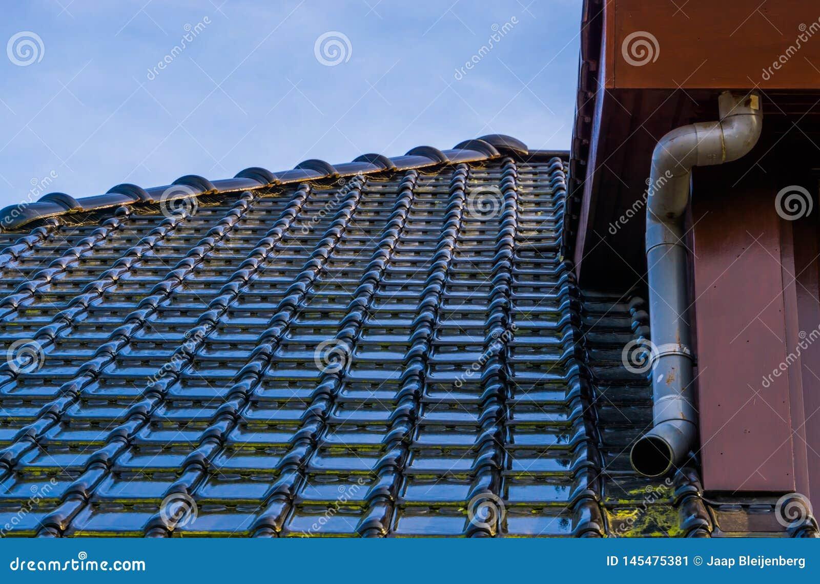 Στέγη με τη μαύρη στιλπνή επικεράμωση στεγών και έναν σωλήνα αποχέτευσης, σύγχρονο ολλανδικό υπόβαθρο αρχιτεκτονικής