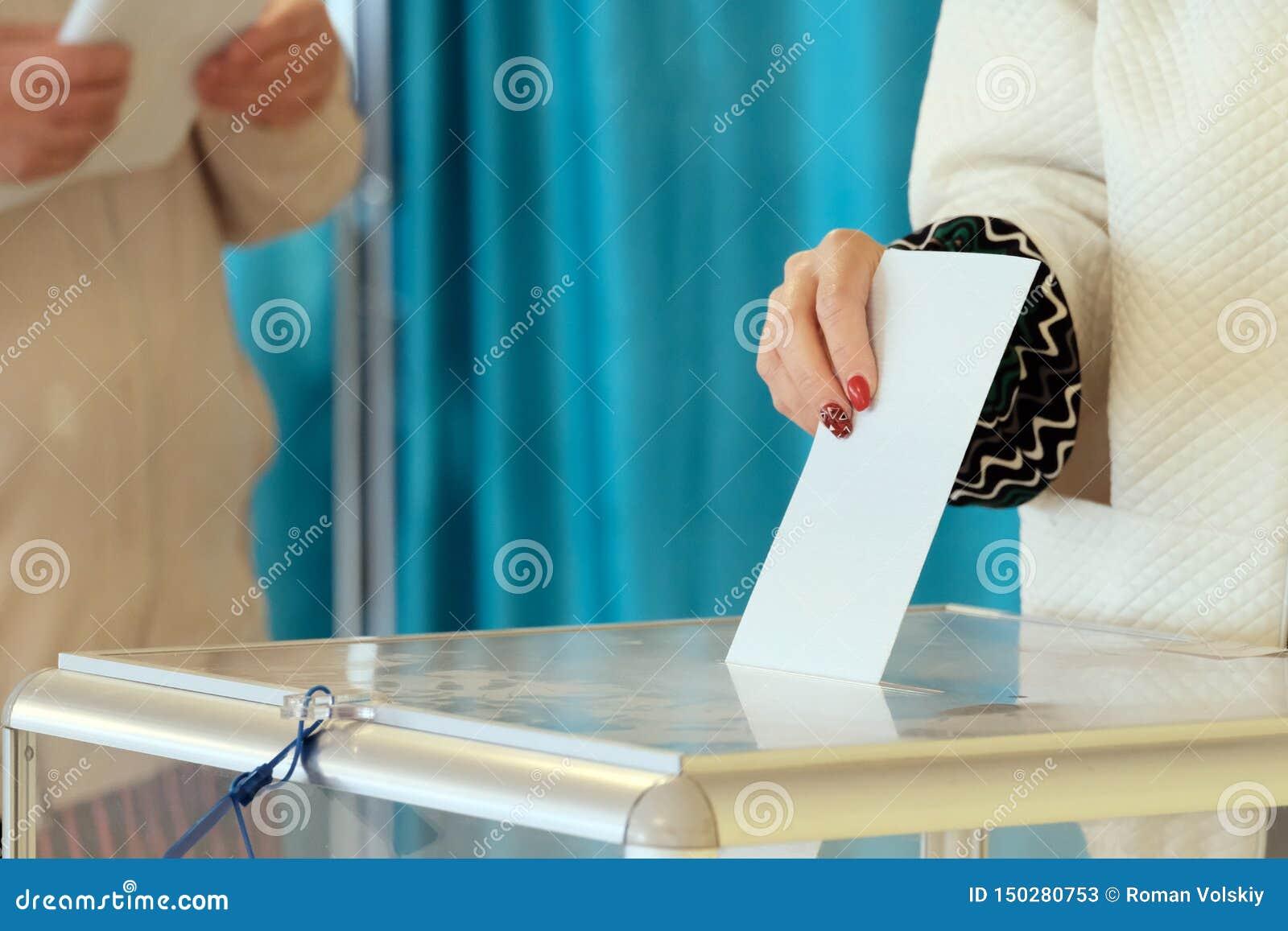 Σταθμός ψηφοφορίας Σε εθνικό επίπεδο ψηφοφορία, εκλογές Το χέρι ενός κοριτσιού με ένα όμορφο μανικιούρ χαμηλώνει την ψήφο σε έναν