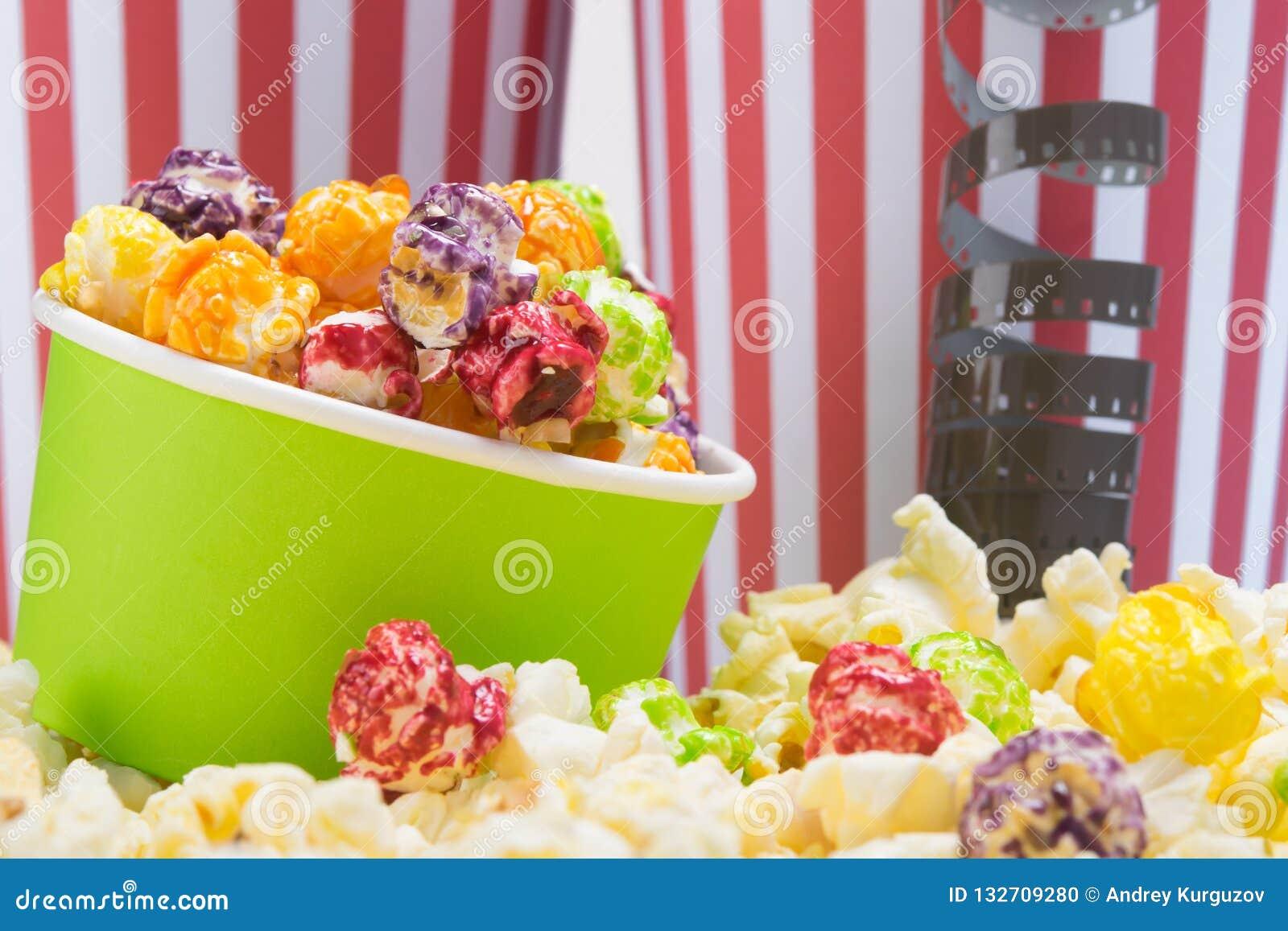 Στα πλαίσια των κόκκινων και άσπρων λωρίδα-γυαλιών, ζωηρόχρωμο popcorn, που περιβάλλεται από τα αλατισμένα σιτάρια
