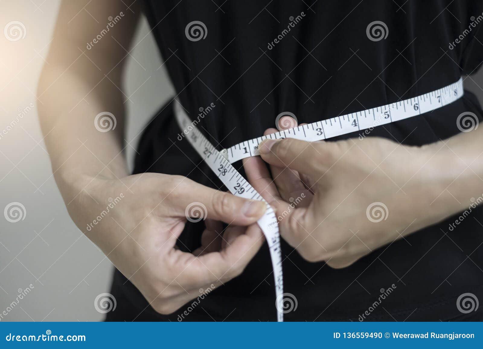 Στενές επάνω γυναίκες έννοιας διατροφής που μετρούν την περιφέρεια μέσης