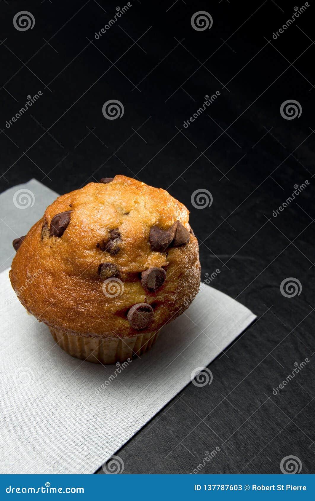 Στενή άποψη εύγευστο Muffin τσιπ σοκολάτας με την γκρίζα πετσέτα στο σκοτεινό υπόβαθρο