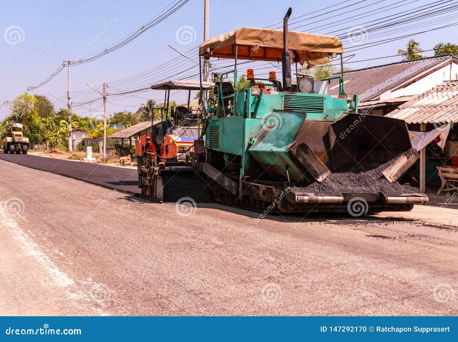 Στενή άποψη σχετικά με τους εργαζομένους και τις ασφαλτώνοντας μηχανές, εργαζόμενοι που κατασκευάζουν την άσφαλτο στη οδοποιία