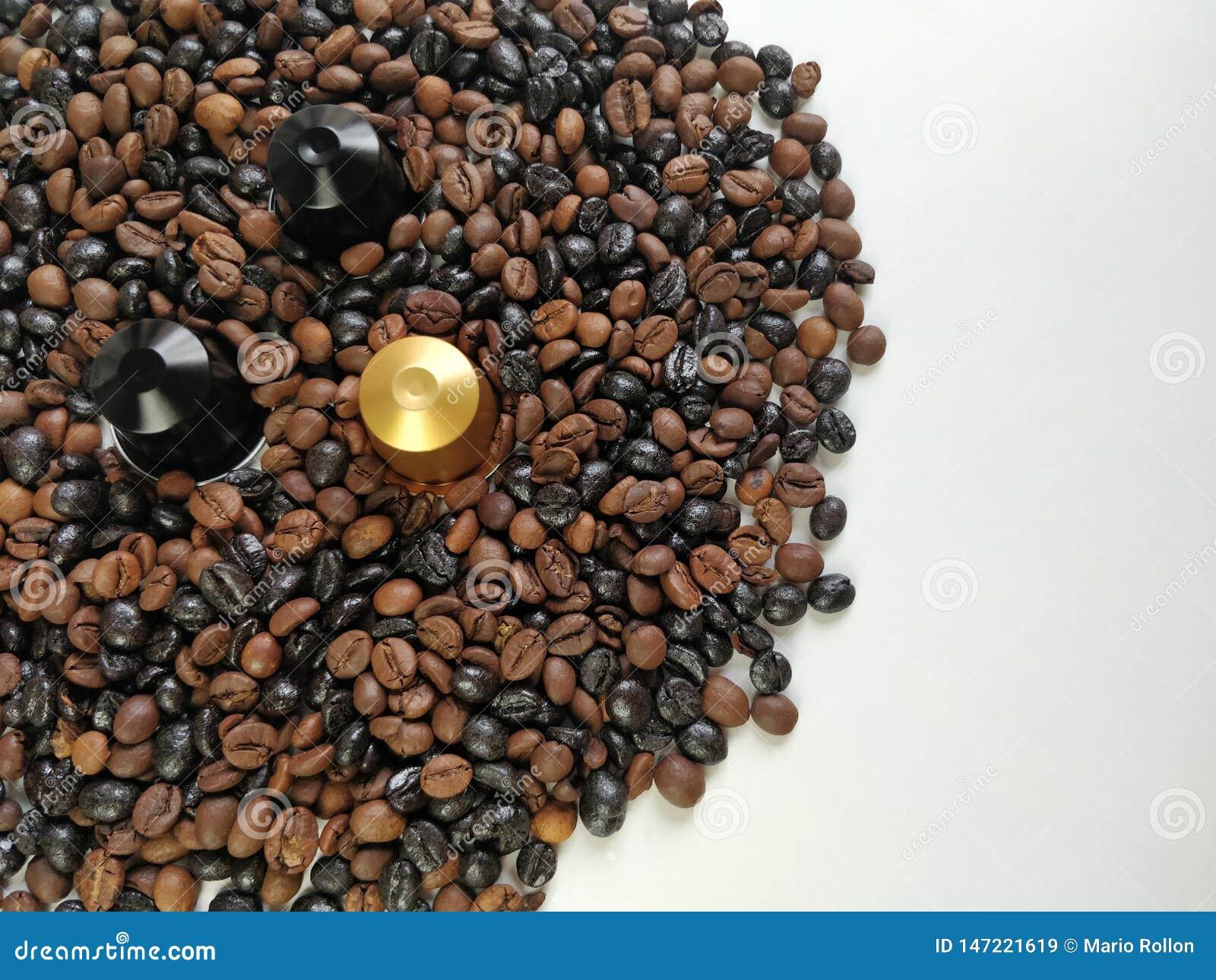 Στενή άποψη τριών καψών καφέ που περιβάλλονται από τα φασόλια καφέ με το κενό διάστημα