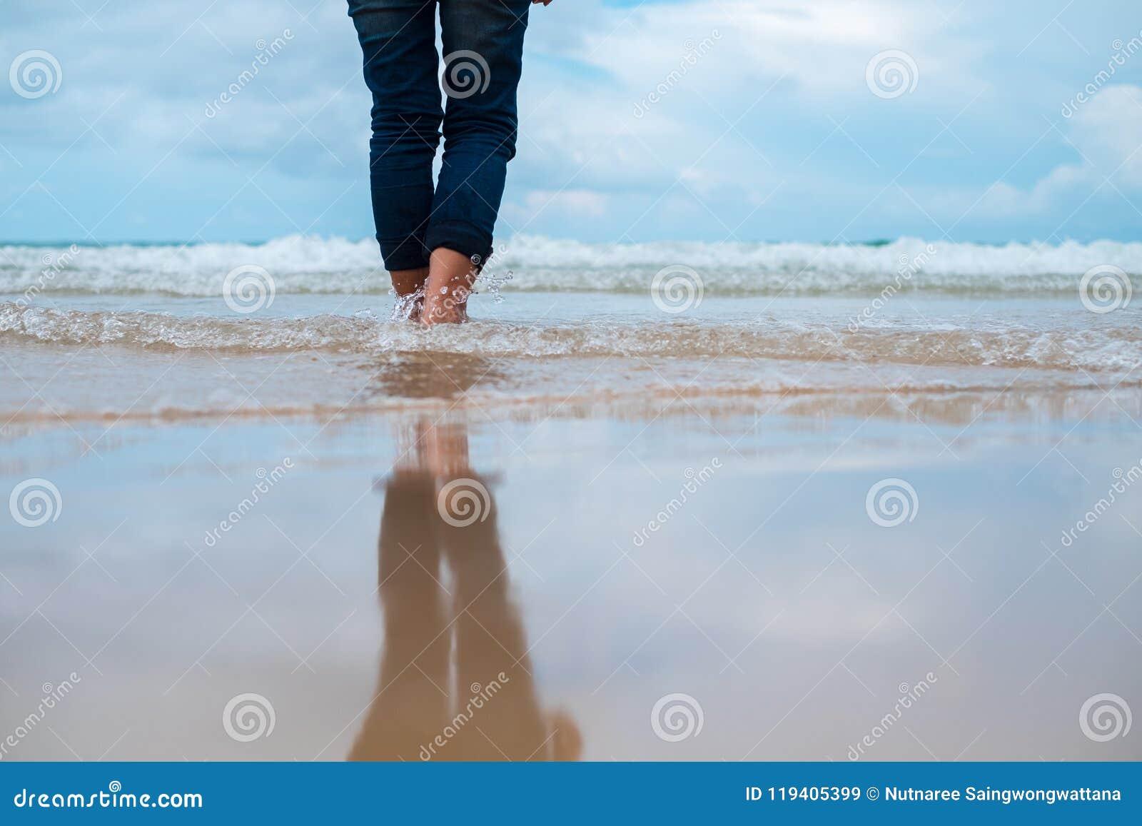 Στενή επάνω καθυστέρηση υποβάθρου φύσης της γυναίκας που στέκεται μόνο στην παραλία
