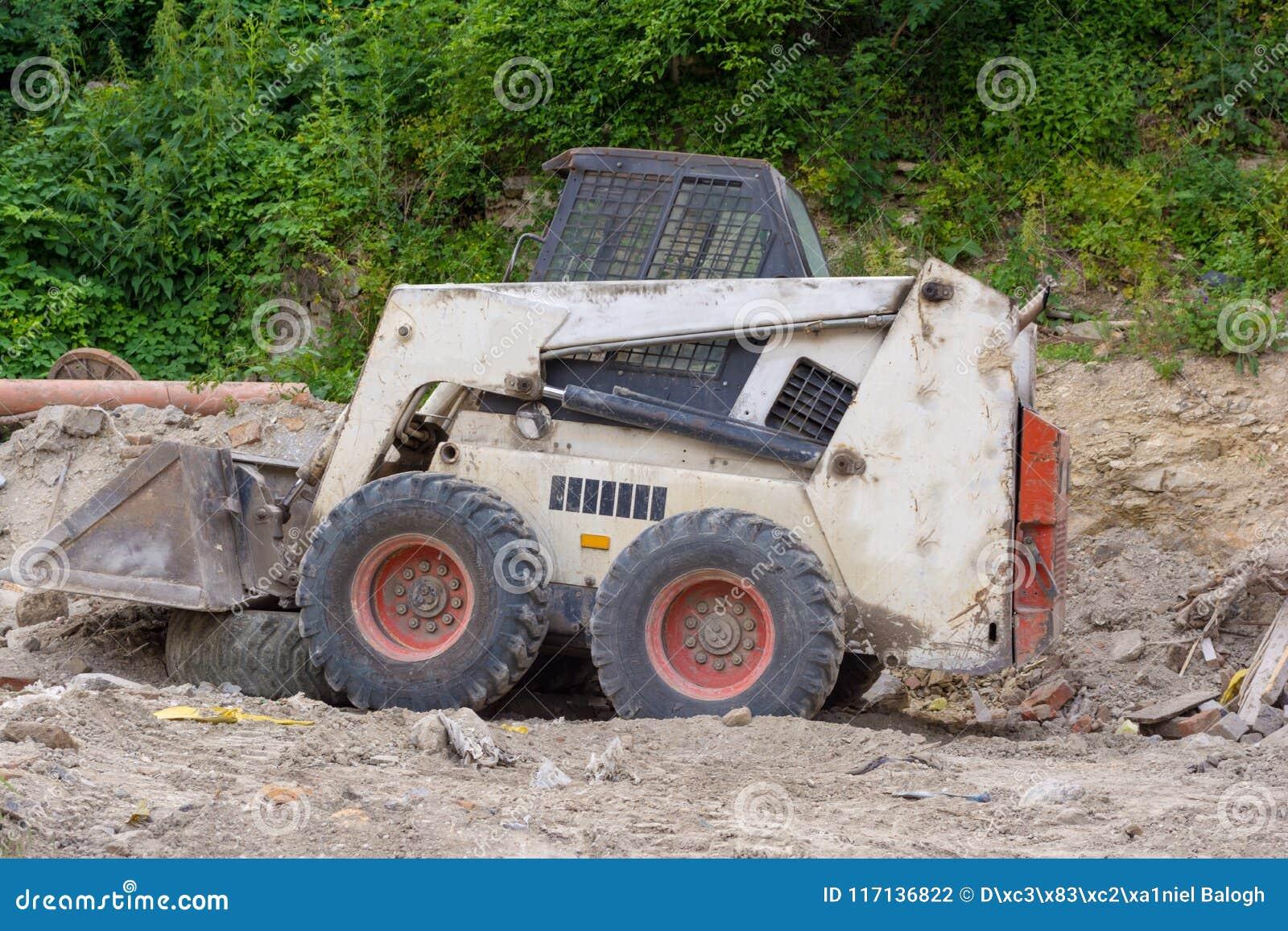Στενός ένας επάνω ενός άσπρου bobcat s550 ή του φορτωτή ολισθήσεων στο εργοτάξιο οικοδομής