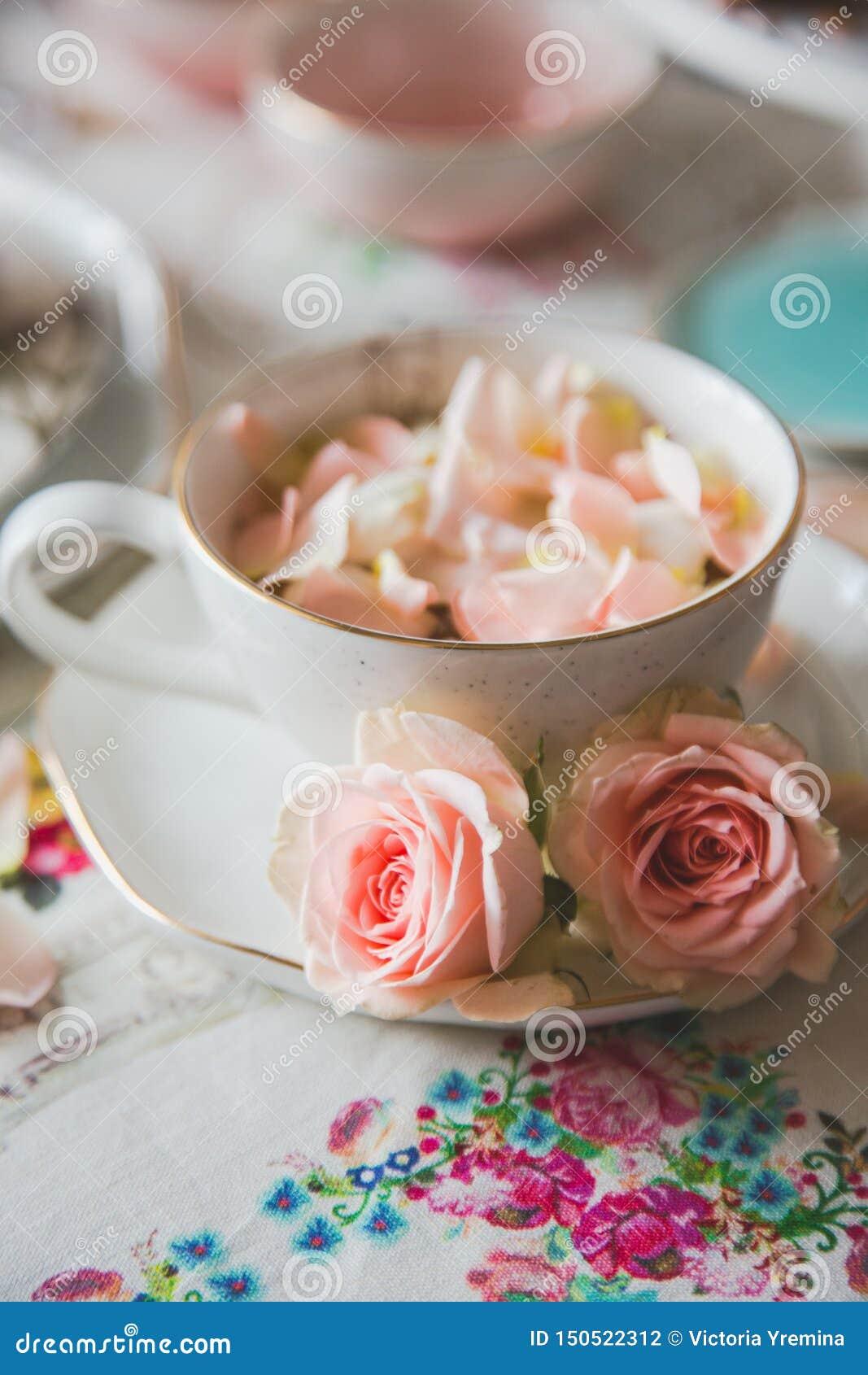 Στενός ένας επάνω ενός φλυτζανιού με το τσάι που διακοσμείται με τα τριαντάφυλλα