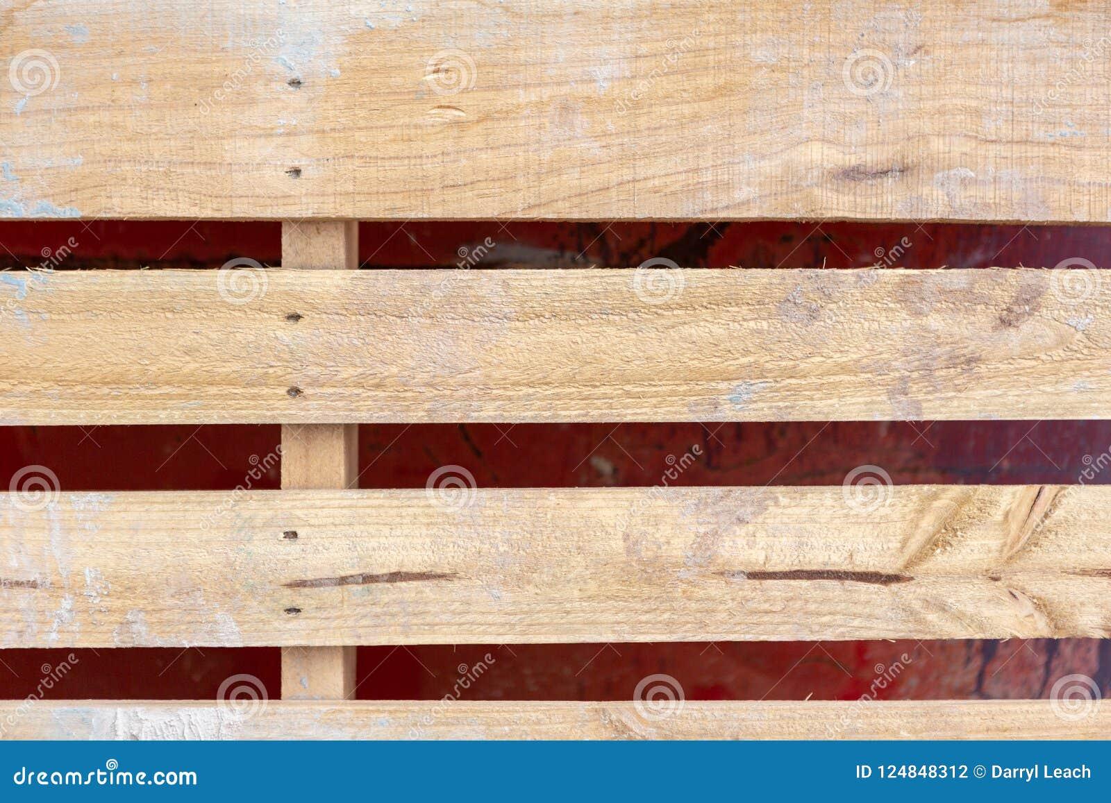 Στενός ένας επάνω μιας ξύλινης παλέτας τούβλου που κλίνει ενάντια σε ένα κόκκινο μετάλλων