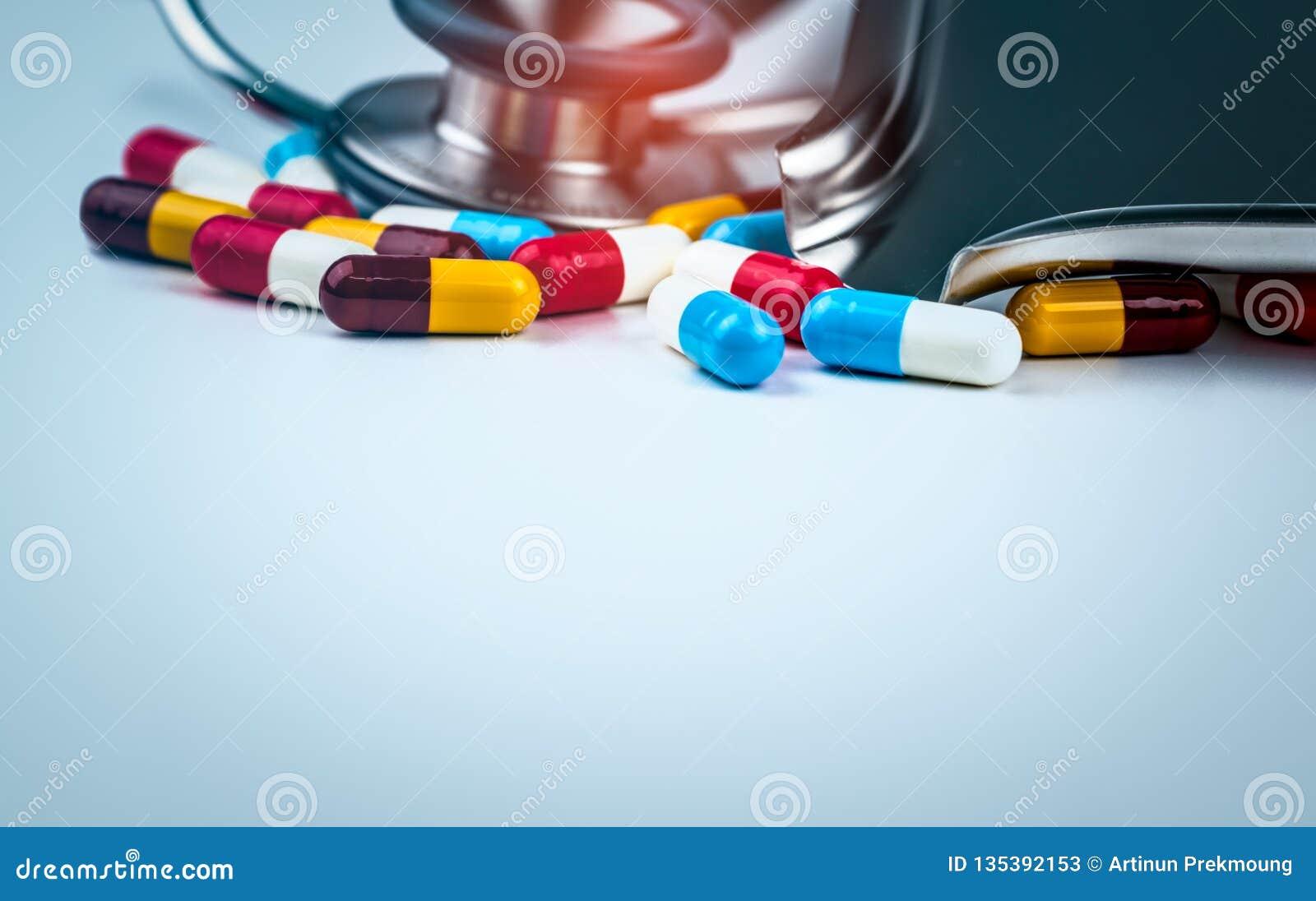 Στηθοσκόπιο με το σωρό των ζωηρόχρωμων αντιβιοτικών χαπιών καψών στον άσπρο πίνακα με το δίσκο φαρμάκων Αντιμικροβιακή αντίσταση