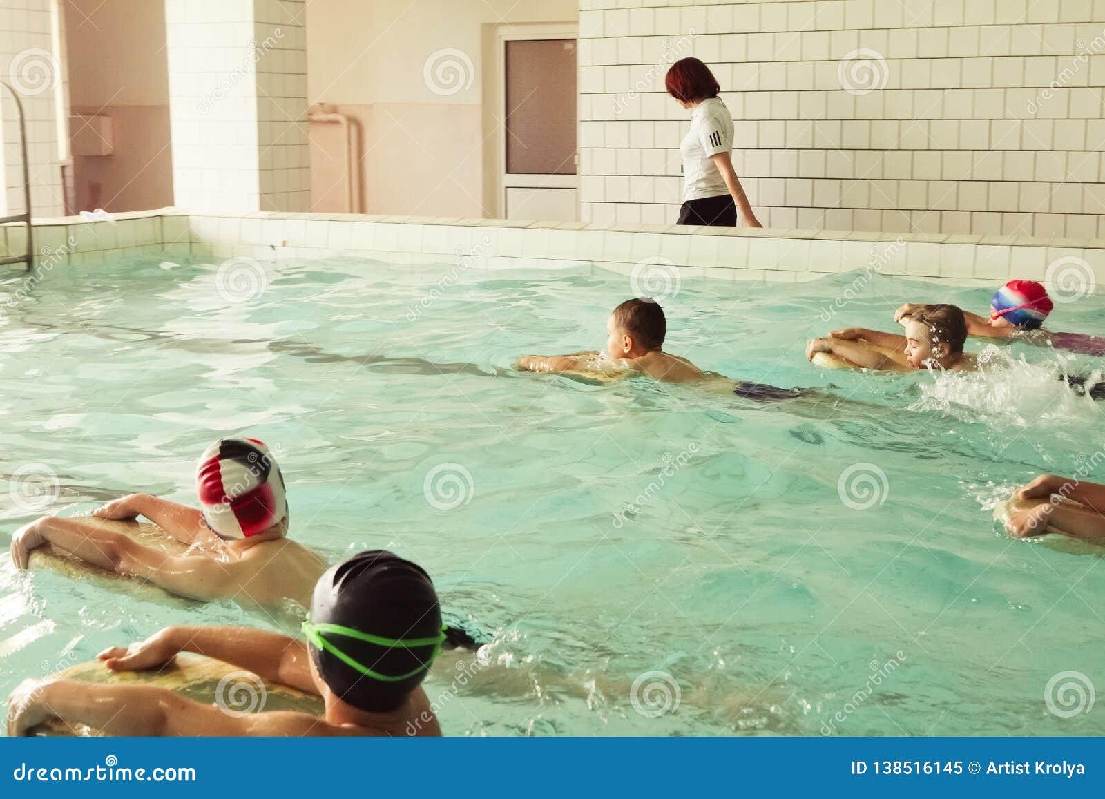 Στοιχειώδη παιδιά σχολείου μέσα στο μάθημα δεξιοτήτων κολύμβησης