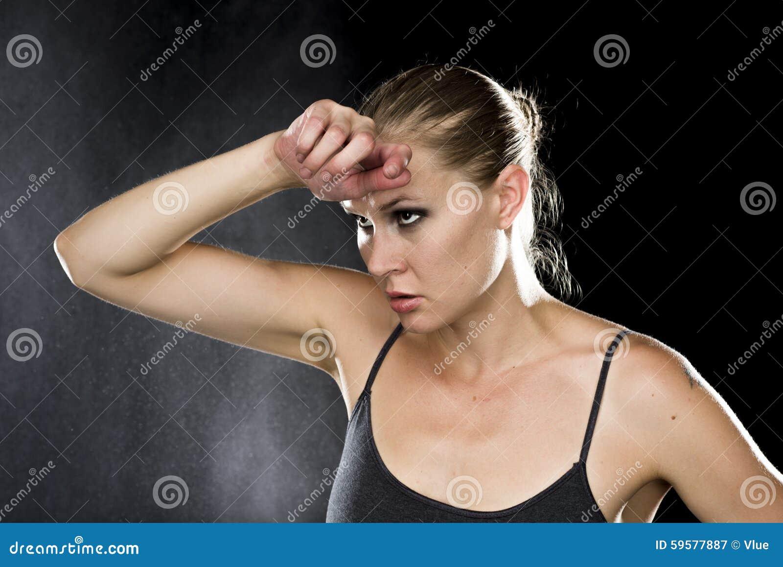 Στοχαστική αθλητική γυναίκα με το χέρι στο μέτωπο