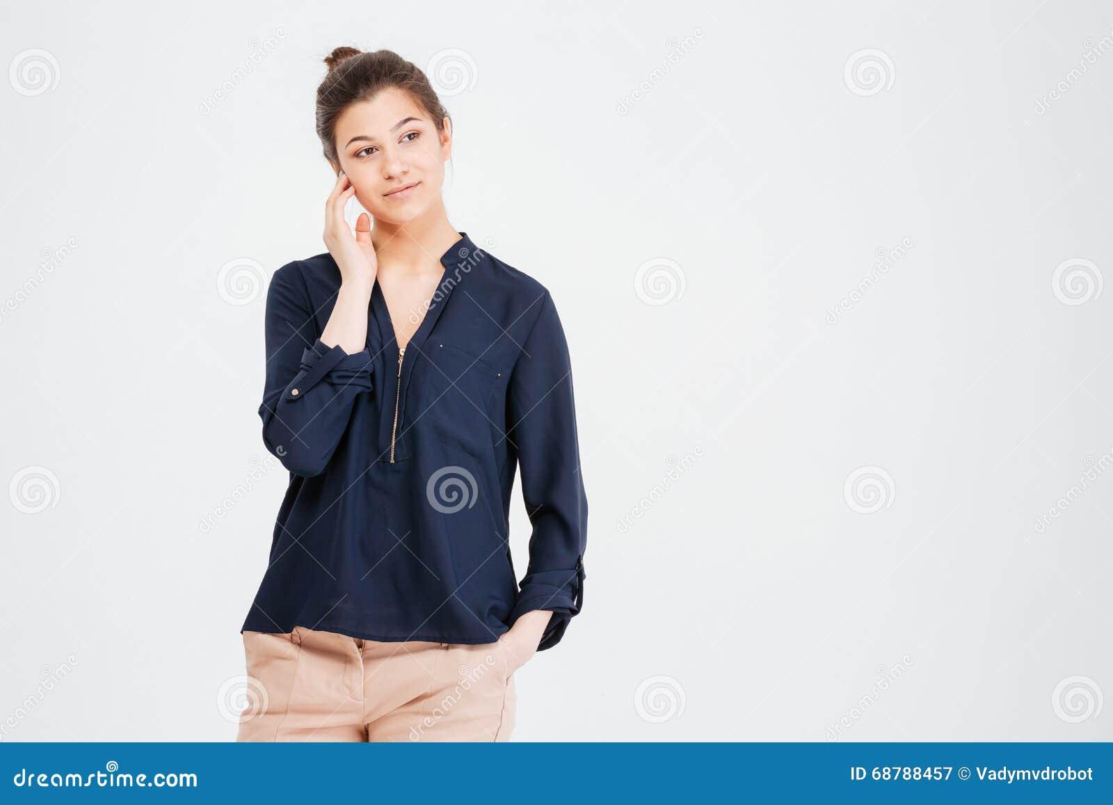 Στοχαστική αρκετά νέα γυναίκα που στέκεται και που σκέφτεται