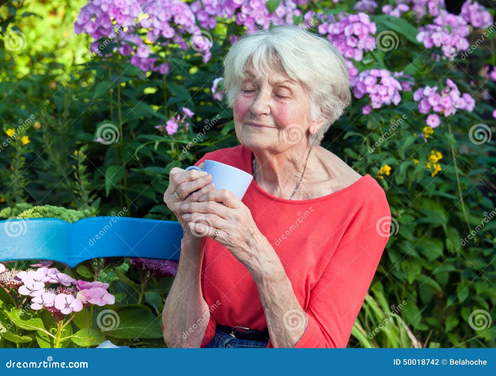 Στοχαστική ηλικιωμένη γυναίκα με τον καφέ στον κήπο