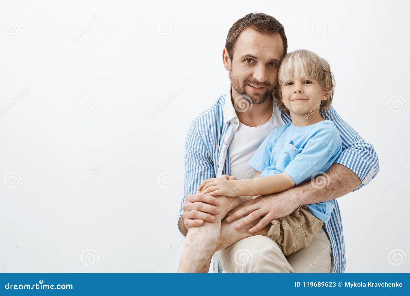 Στούντιο που πυροβολείται του ευτυχών θετικών πατέρα και του γιου με το vitiligo, αγκαλιάζοντας και χαμογελώντας ευρέως στη κάμερ