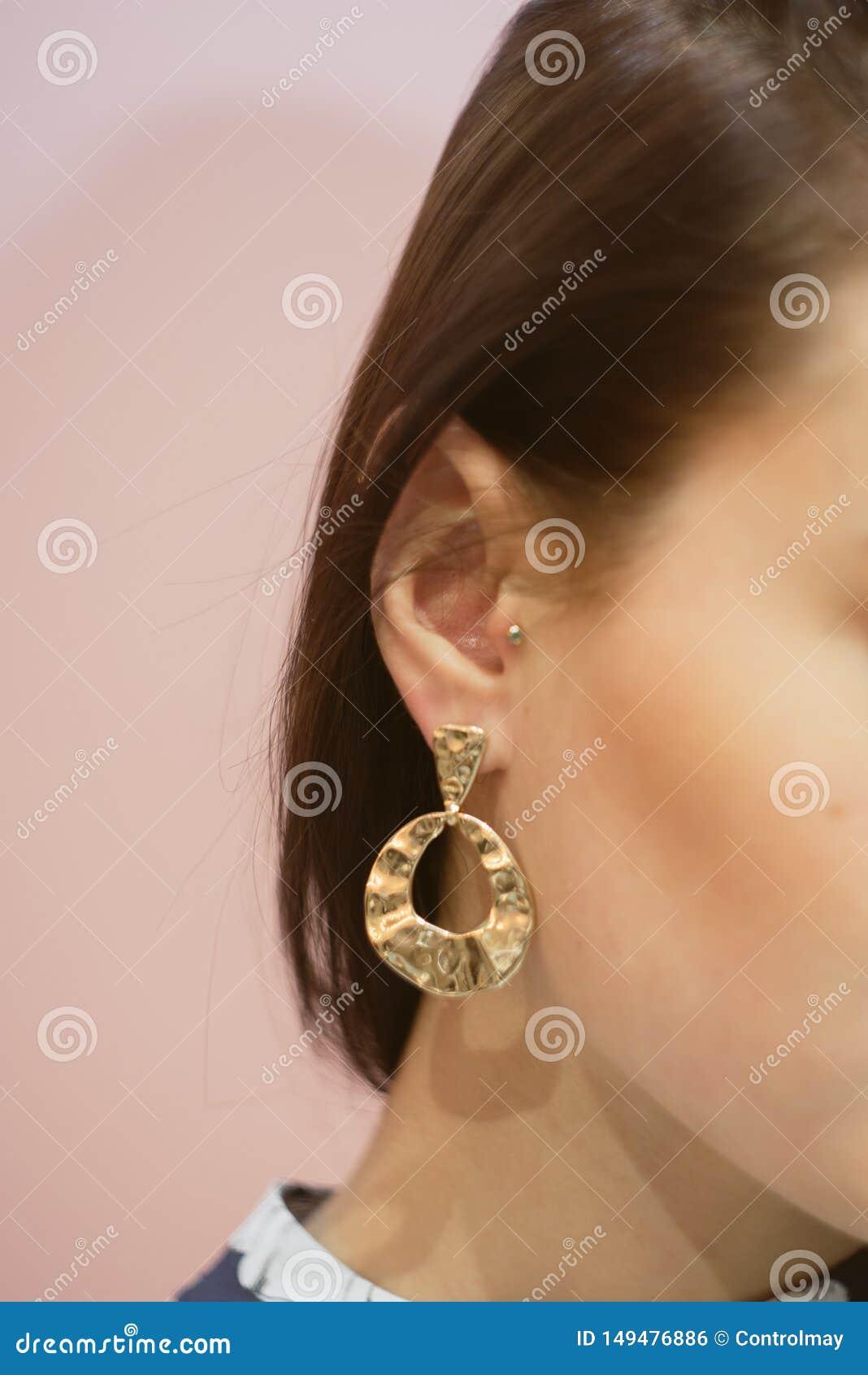 στρογγυλά χρυσά σκουλαρίκια στο αυτί ενός brunette σε ένα ρόδινο υπόβαθρο κρητιδογραφιών