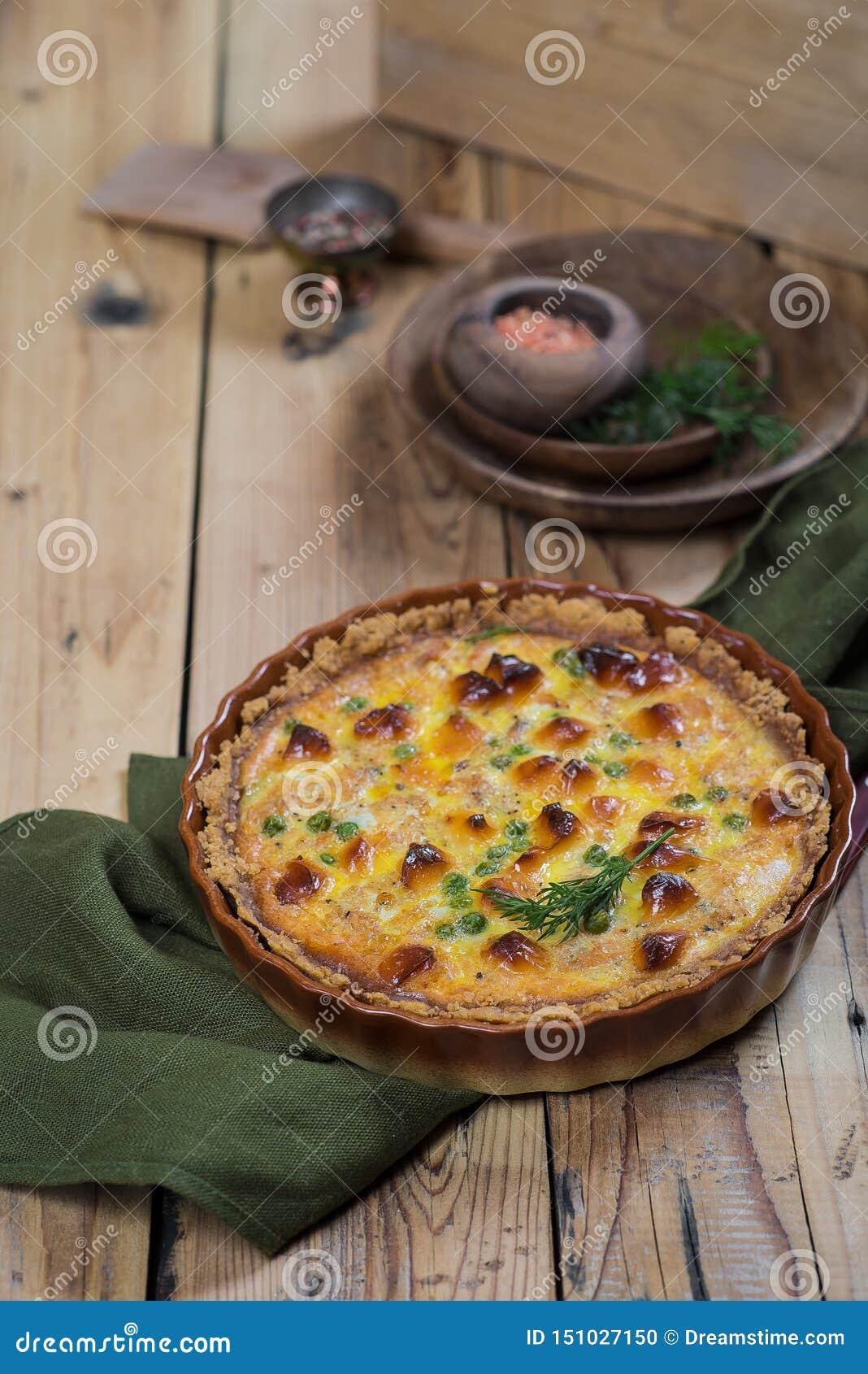 Στρογγυλή κατακόκκινη ανοικτή πίτα με την πλήρωση λαχανικών και τυριών