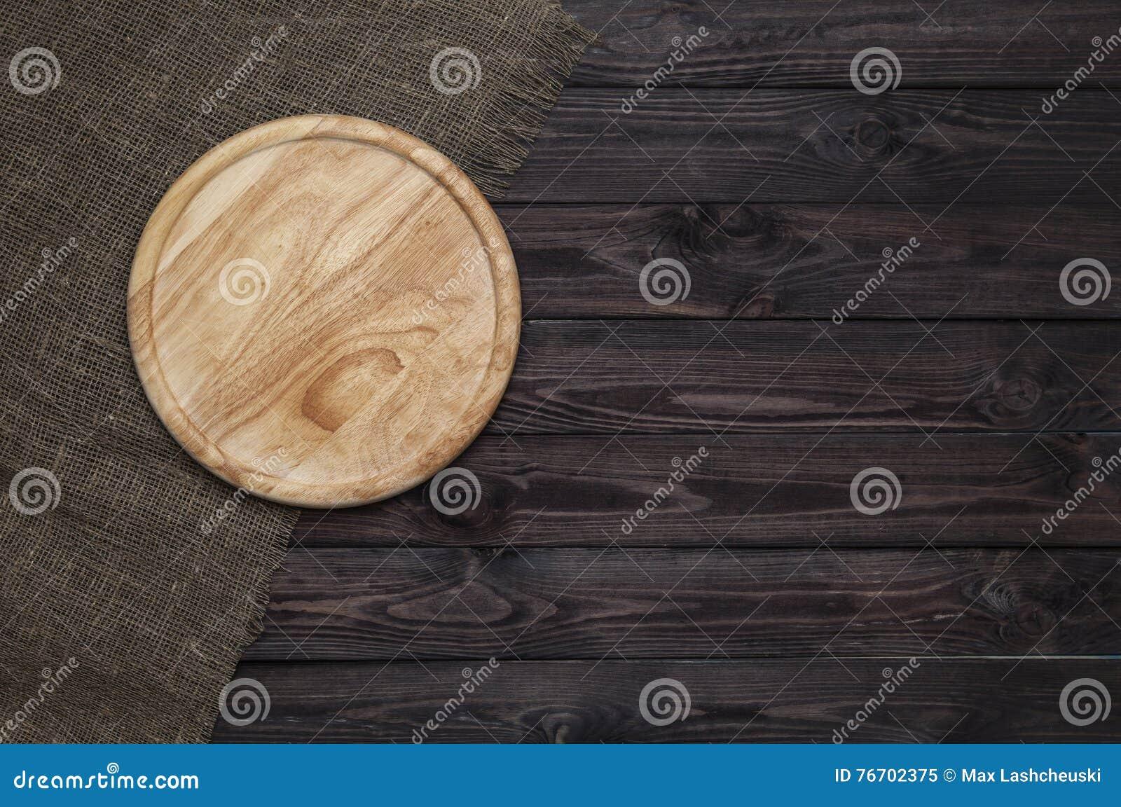 Στρογγυλός τέμνων πίνακας στο σκοτεινό ξύλινο πίνακα