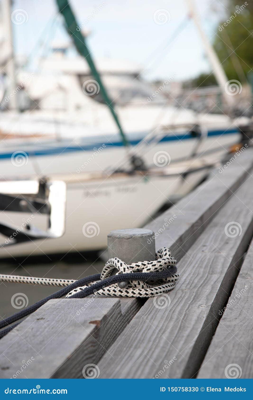 Στυλοβάτης για τη σύνδεση των βαρκών σε μια ξύλινη αποβάθρα Στυλίσκος με δύο σχοινιά στα αλιευτικά σκάφη αποβαθρών στις θολωμένες
