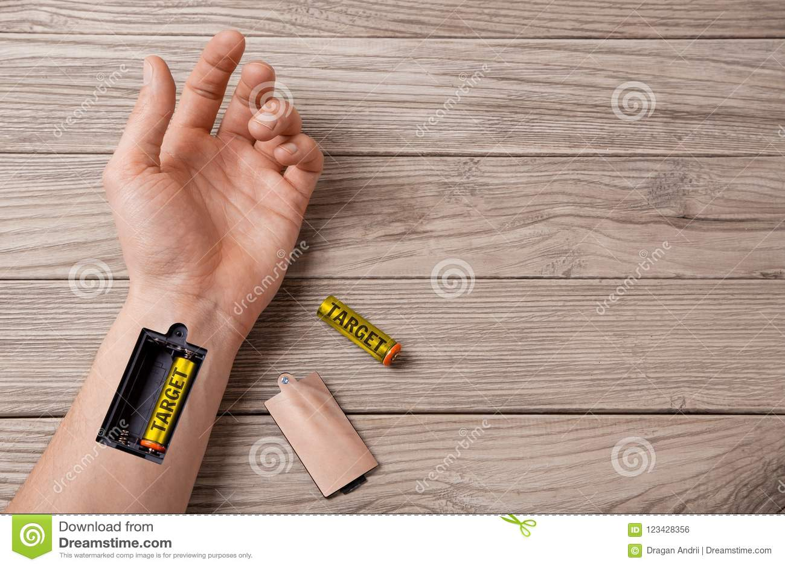 Στόχος Χέρι ενός ατόμου με την αυλάκωση για τη φόρτιση του στόχου μπαταριών