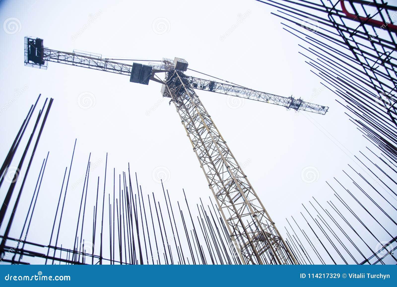 Συγκεκριμένοι στυλοβάτες στο βιομηχανικό εργοτάξιο οικοδομής Οικοδόμηση του ουρανοξύστη με το γερανό, τα εργαλεία και τους ενισχυ