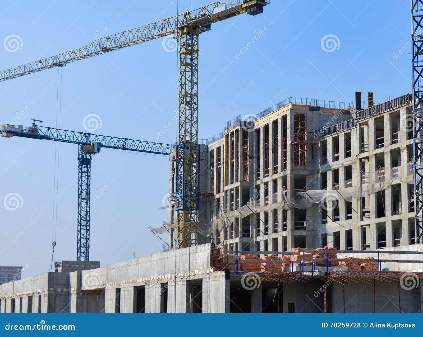Συγκεκριμένο εργοτάξιο οικοδομής οικοδόμησης με τους γερανούς στο μπλε ουρανό