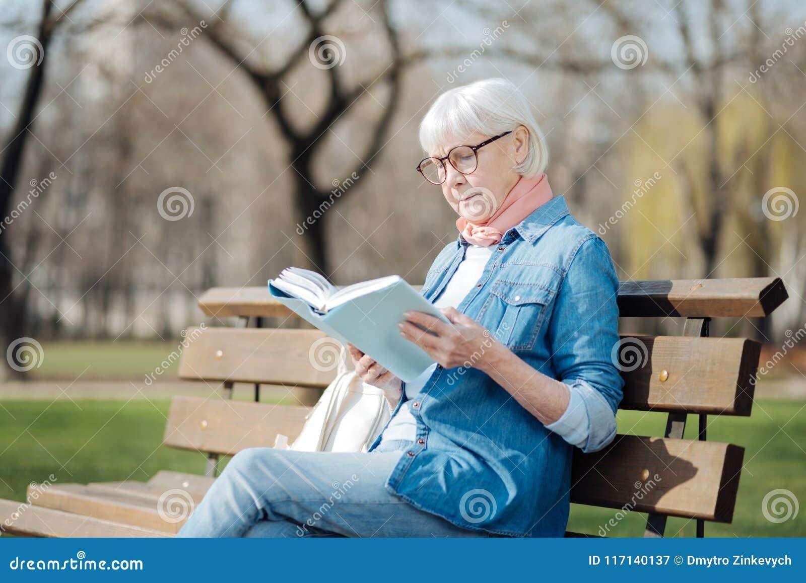 Συγκεντρωμένη ηλικιωμένη γυναίκα που διαβάζει ένα βιβλίο