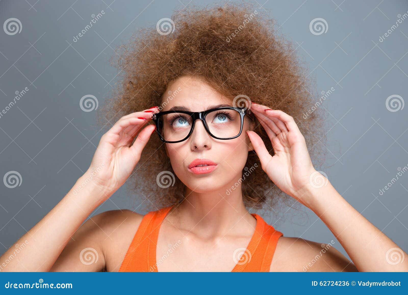 Συγκεντρωμένη νέα σγουρή γυναίκα στα μαύρα γυαλιά που ανατρέχει