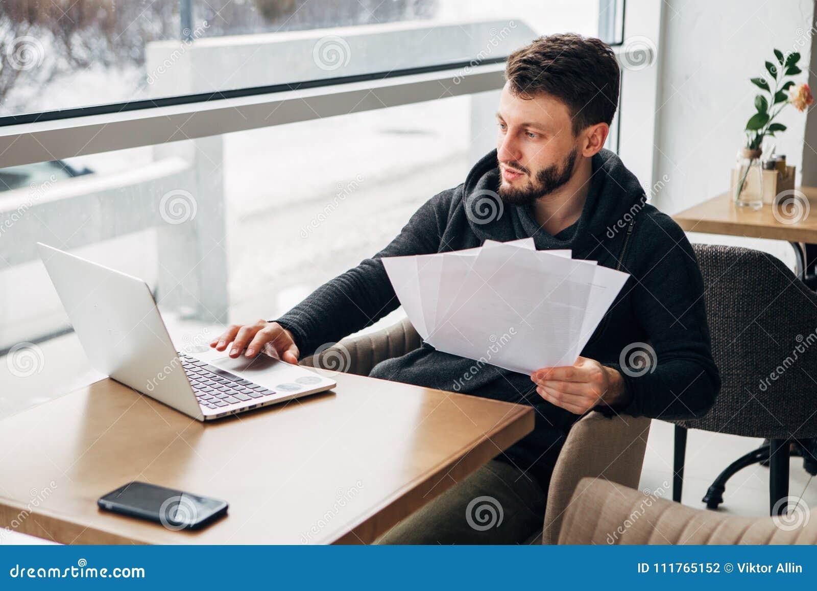 Συγκεντρωμένος νέος γενειοφόρος επιχειρηματίας που φορά το μαύρο αστικό καφέ lap-top μπλουζών λειτουργώντας