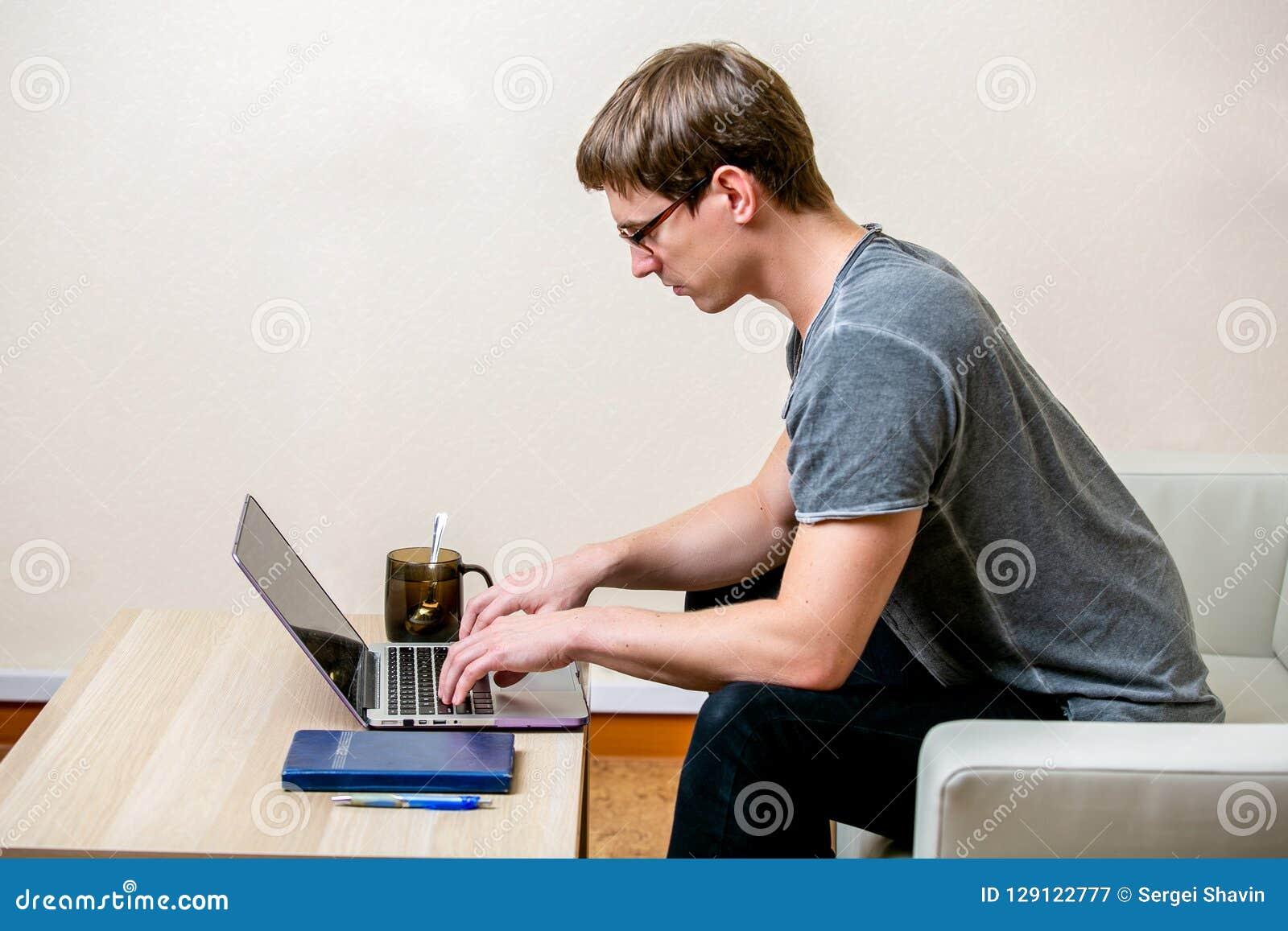 Συγκεντρωμένος νεαρός άνδρας με τα γυαλιά που λειτουργούν σε ένα lap-top σε ένα Υπουργείο Εσωτερικών Τύπος σε ένα πληκτρολόγιο κα