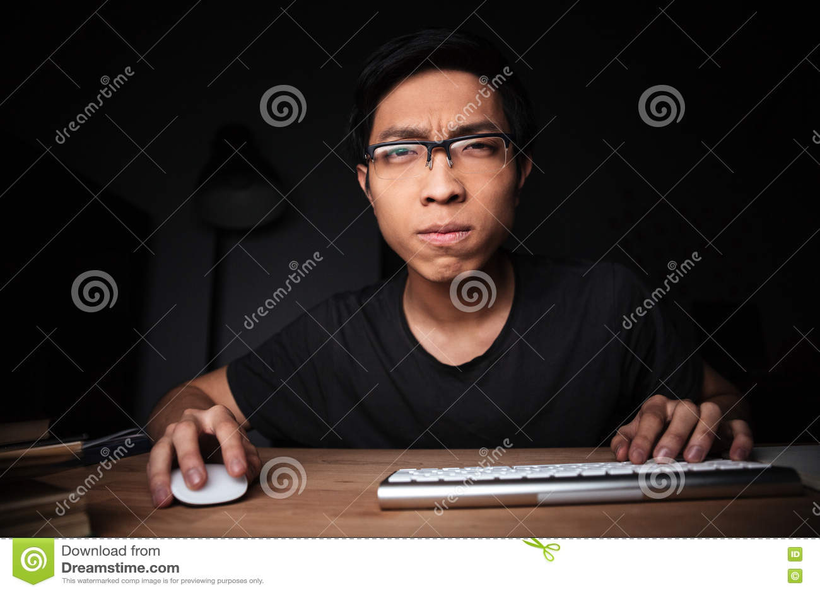 Συγκεντρωμένο άτομο στα γυαλιά που λειτουργούν με τον υπολογιστή