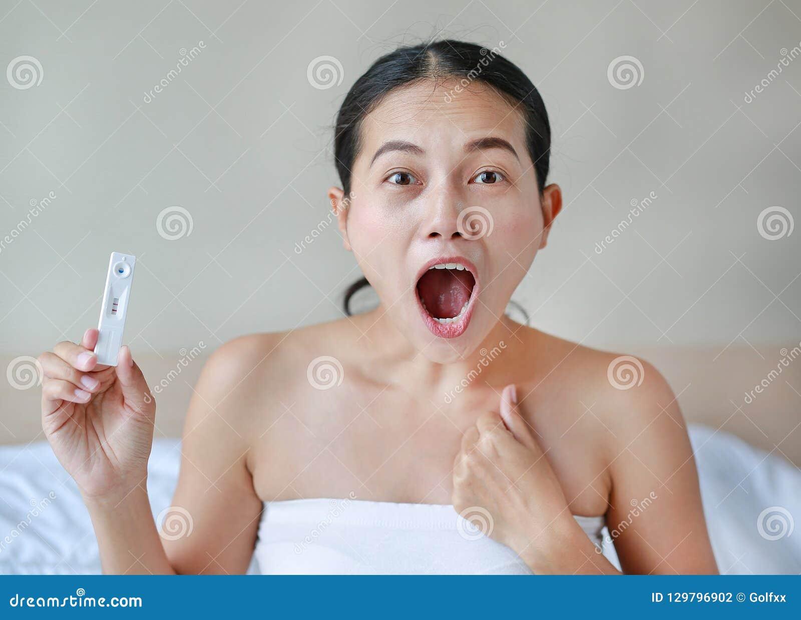 Συγκινημένη νέα γυναίκα που κρατά τη θετική δοκιμή εγκυμοσύνης
