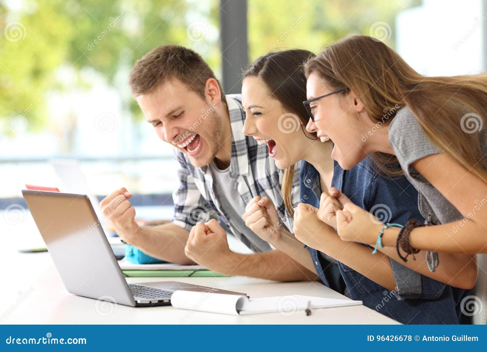 Συγκινημένοι σπουδαστές που διαβάζουν τις καλές ειδήσεις σε μια τάξη