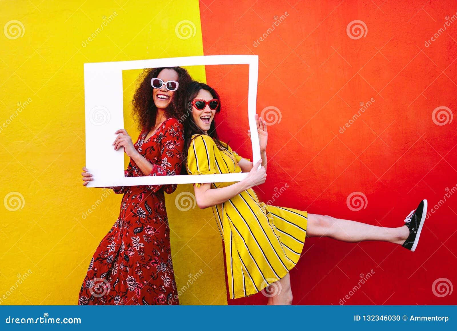 Συγκινημένοι φίλοι κοριτσιών με το κενό πλαίσιο φωτογραφιών