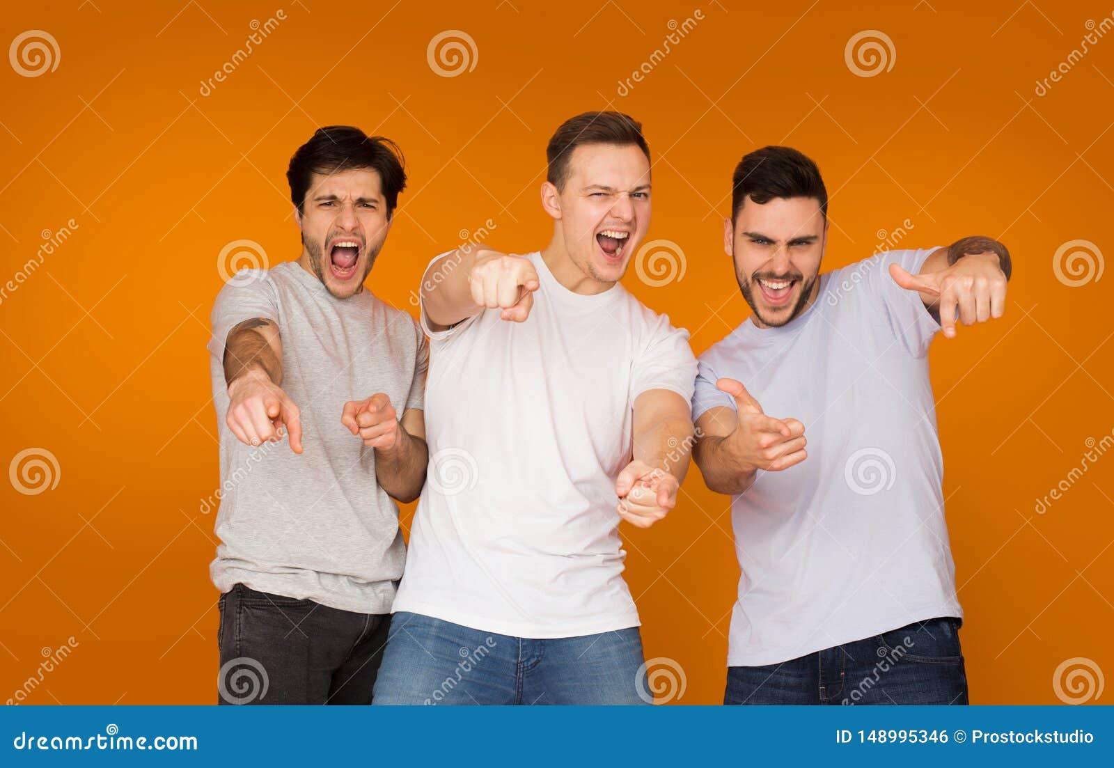 Συγκινημένοι φίλοι που δείχνουν τα δάχτυλα στη κάμερα, πορτοκαλί υπόβαθρο