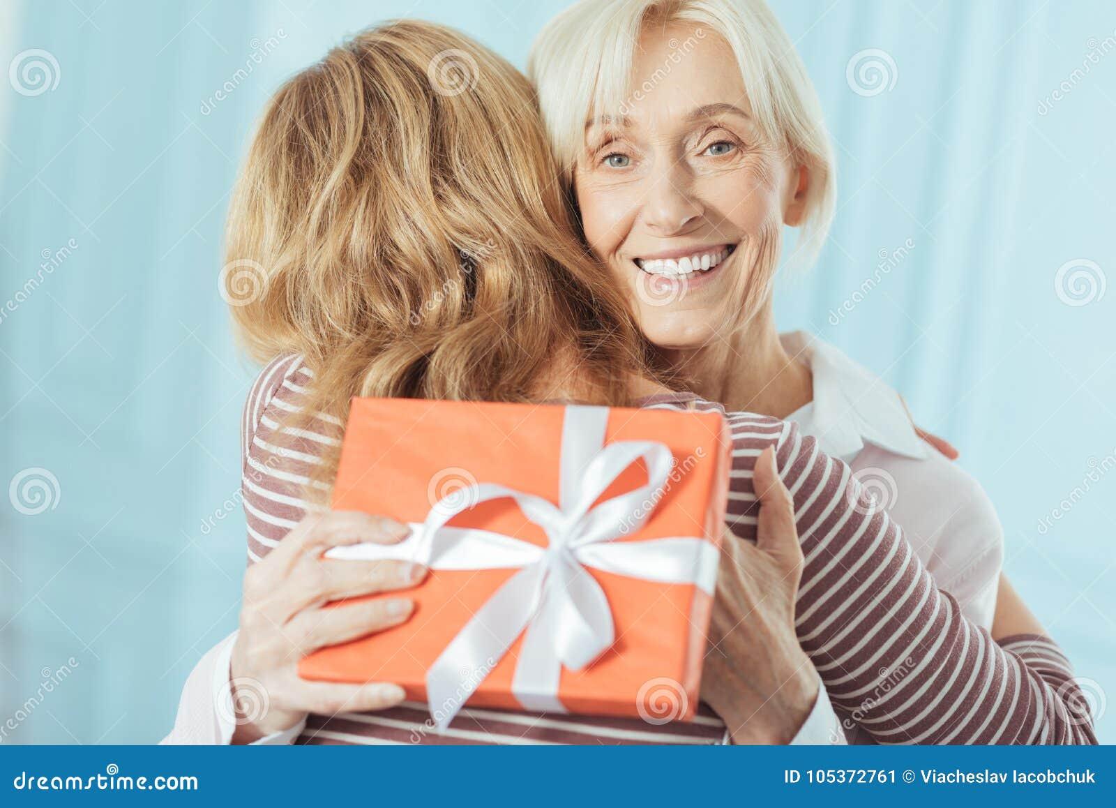 Συγκινημένος συνταξιούχος που στέκεται με ένα παρόν αγκαλιάζοντας τη χαριτωμένη εγγονή της
