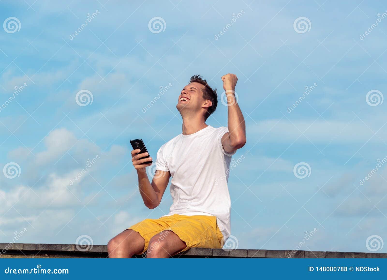 Συγκινημένο άτομο που κρατούν ένα smartphone και μια νίκη σε απευθείας σύνδεση σε έναν τροπικό προορισμό