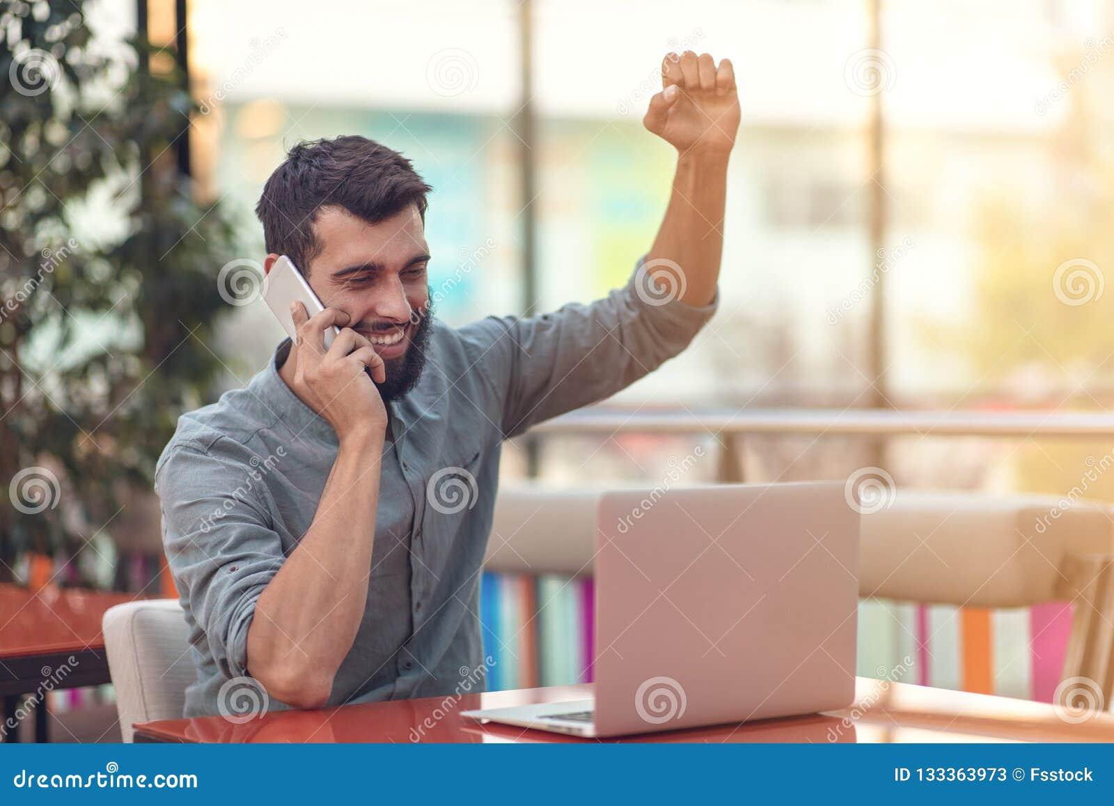 Συγκινημένο ευτυχές γενειοφόρο ηλεκτρονικό ταχυδρομείο ανάγνωσης freelancer με τα αποτελέσματα για τη νίκη στη σύγχρονη σε απευθε