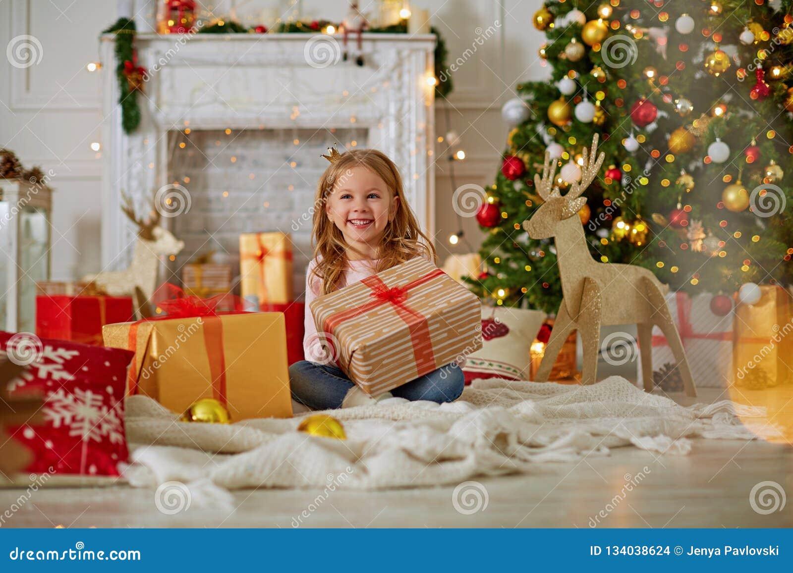 Συγκινημένο περίεργο μικρό κορίτσι που χαμογελά, δώρα Χριστουγέννων ανοίγματος Υπέροχα διακοσμημένα χριστουγεννιάτικο δέντρο και