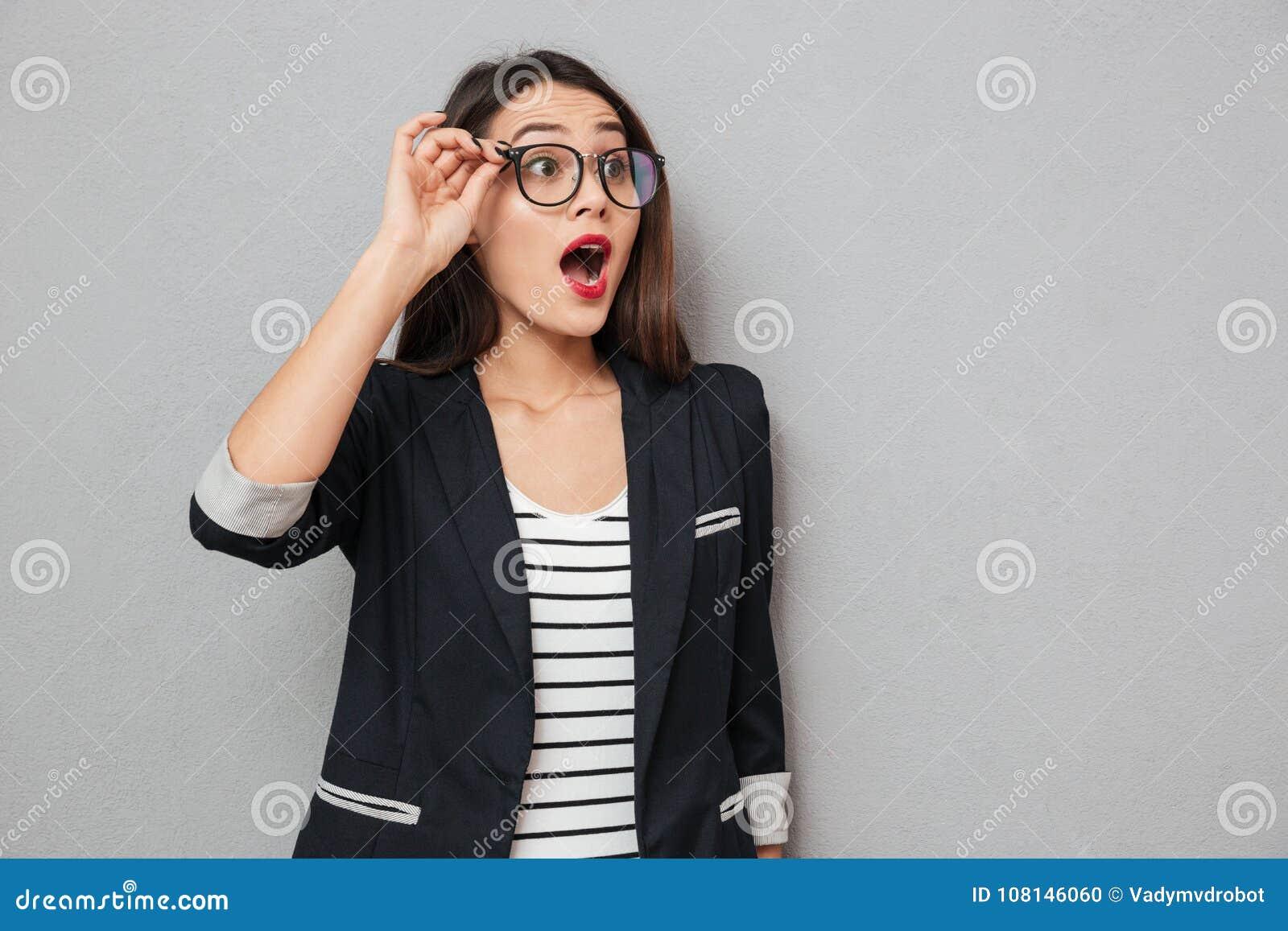 Συγκλονισμένη επιχειρησιακή γυναίκα eyeglasses που κοιτάζει μακριά με το ανοικτό στόμα