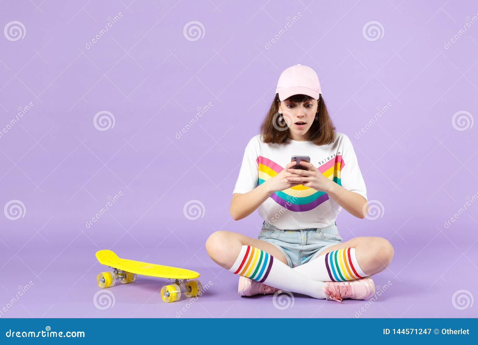 Συγκλονισμένο κορίτσι εφήβων στα ζωηρά ενδύματα που κάθεται κοντά skateboard, που χρησιμοποιεί το κινητό τηλέφωνο, δακτυλογραφώντ