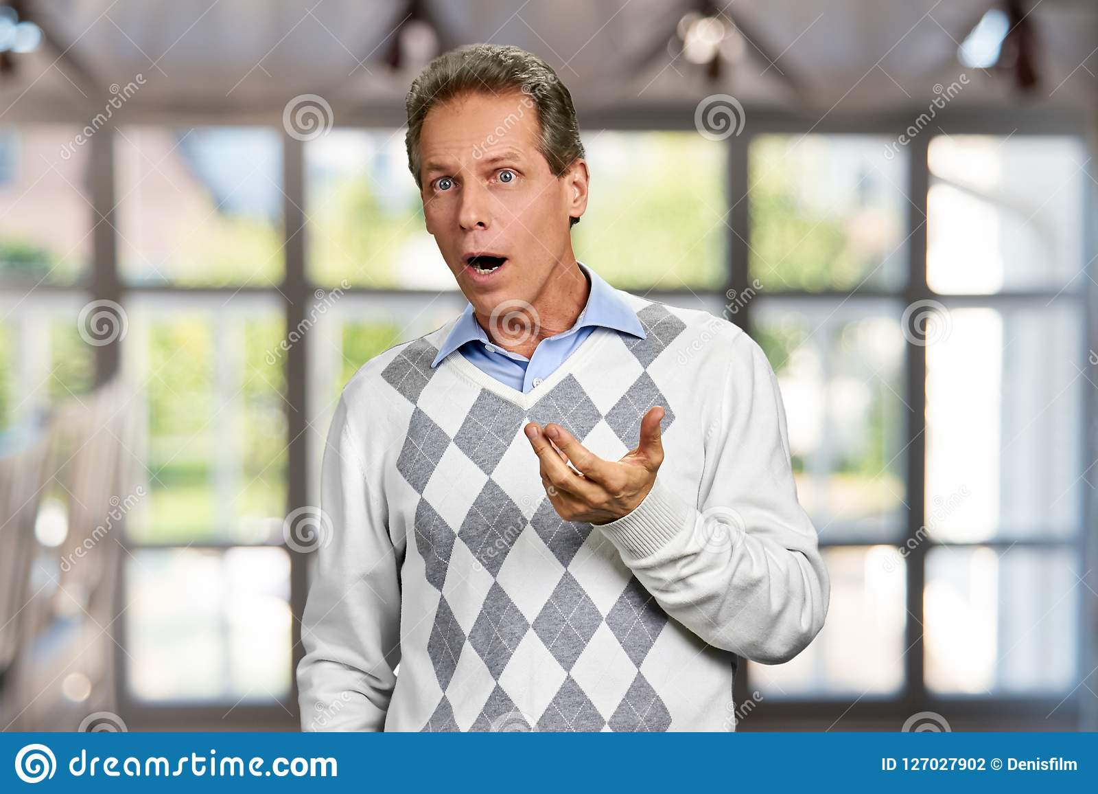 Συγκλονισμένο ώριμο άτομο στο θολωμένο υπόβαθρο