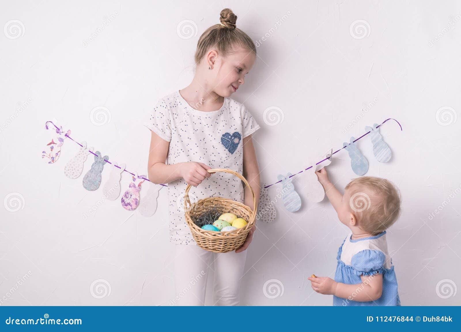 Συγχαρητήρια σε ευτυχές Πάσχα: το κορίτσι κρατά ένα καλάθι με τα χρωματισμένα αυγά από τον άσπρο τοίχο
