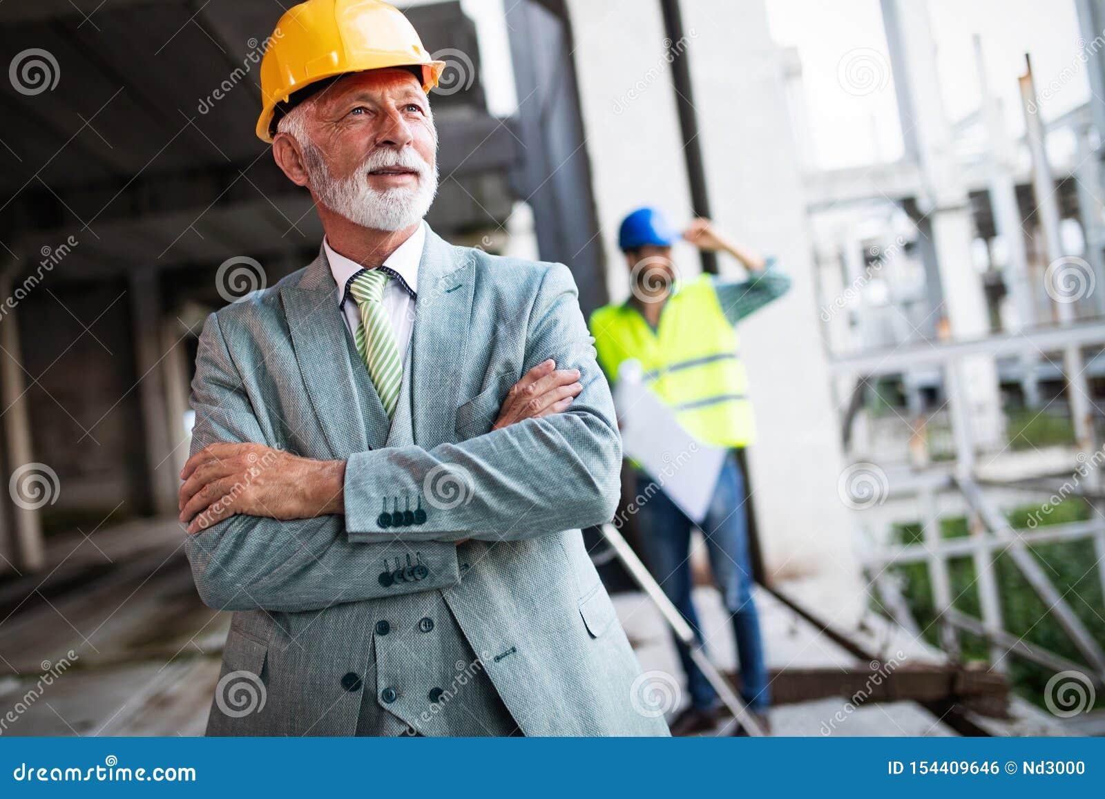 Συζήτηση μηχανικών κατασκευής με τους αρχιτέκτονες στην κατασκευή ή το εργοτάξιο