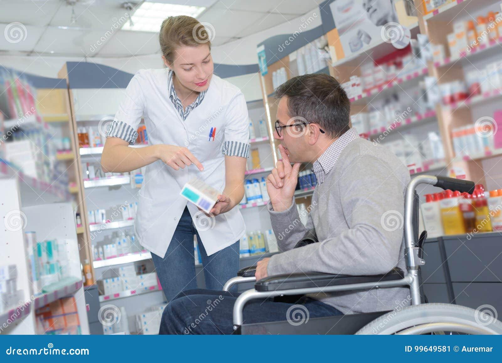 Συμβουλευτικό άτομο φαρμακοποιών στην αναπηρική καρέκλα στο φαρμακείο