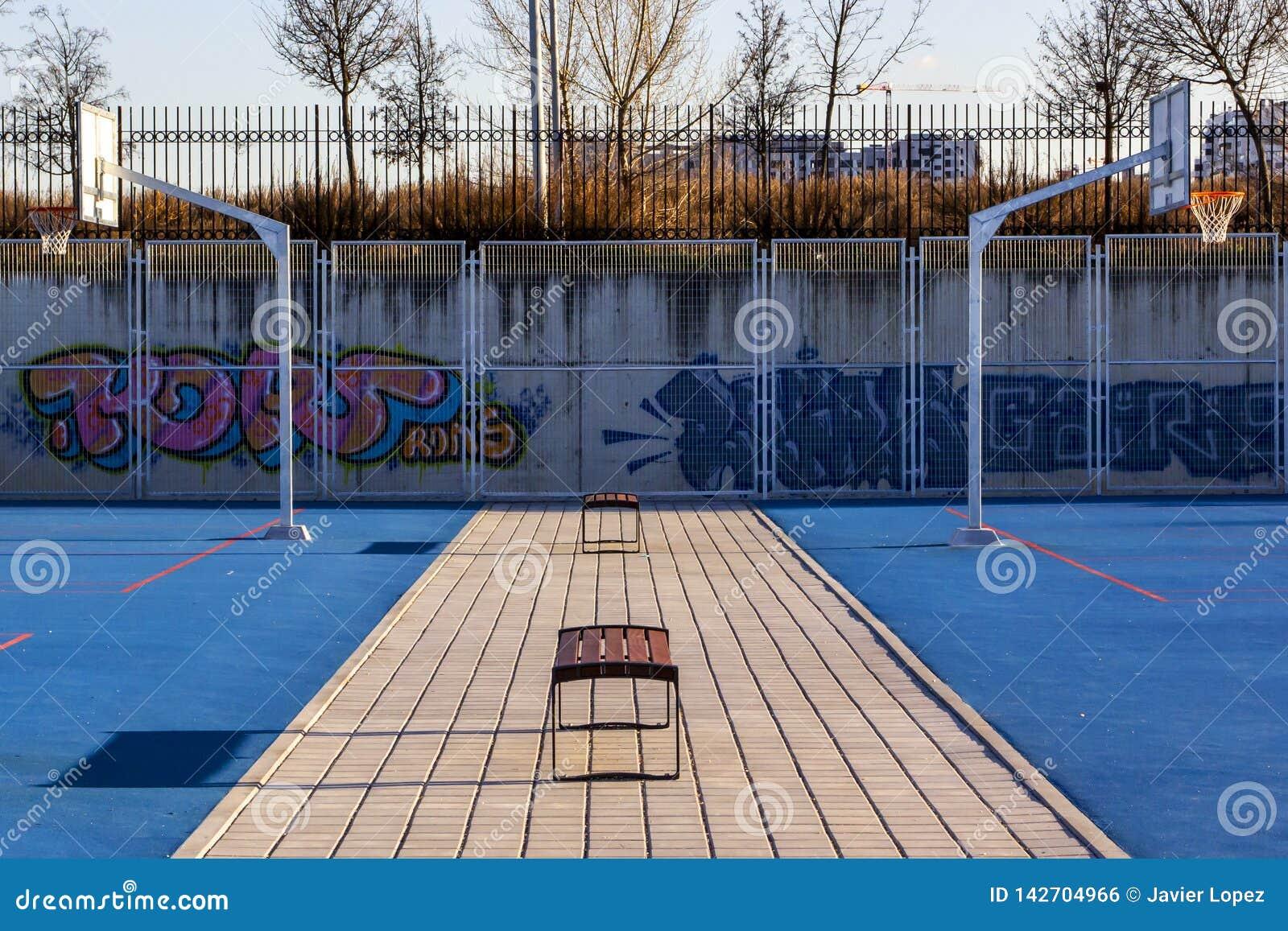 Συμμετρία σε μια μπλε καλαθοσφαίριση plaground με τους πάγκους