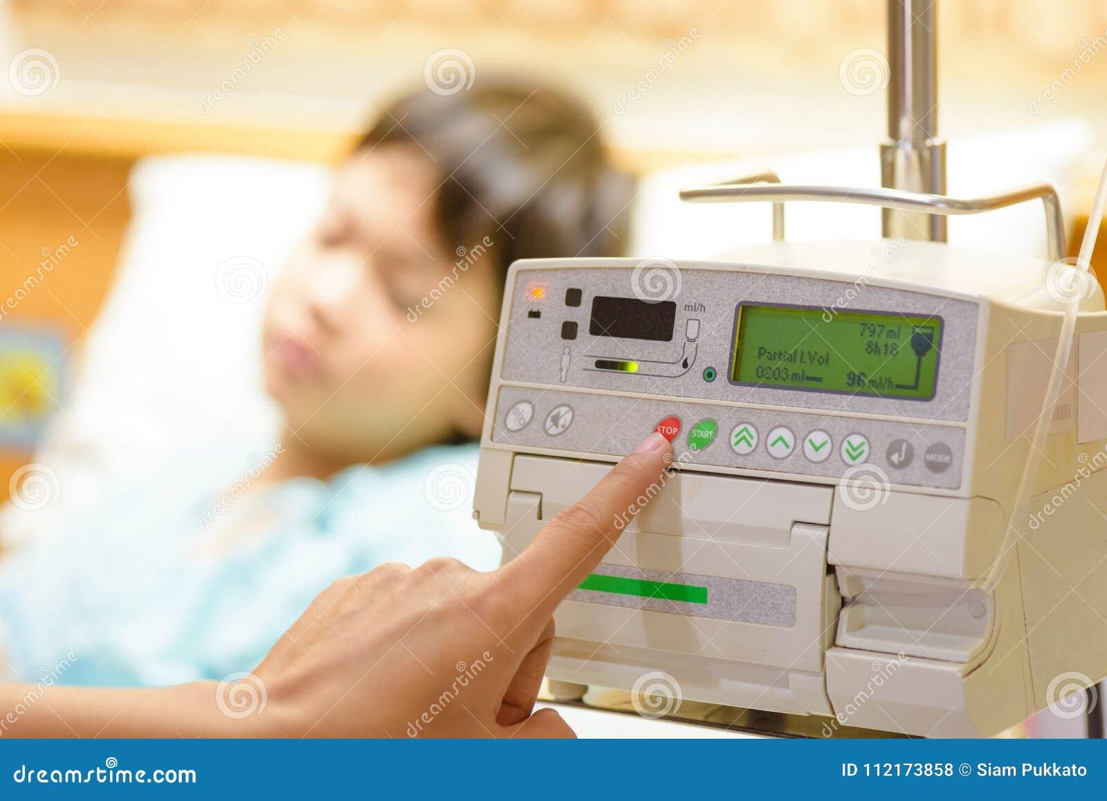 Συμπίεση χεριών νοσοκόμων ` s σε ενδοφλέβια IV σταλαγματιά αντλιών έγχυσης
