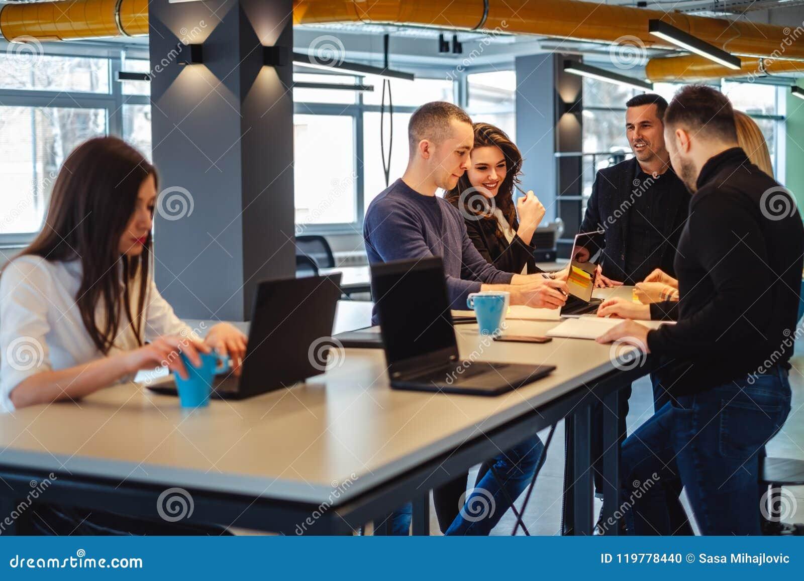 Συνάδελφοι που χαμογελούν εργαζόμενοι στη συνεδρίαση των γραφείων