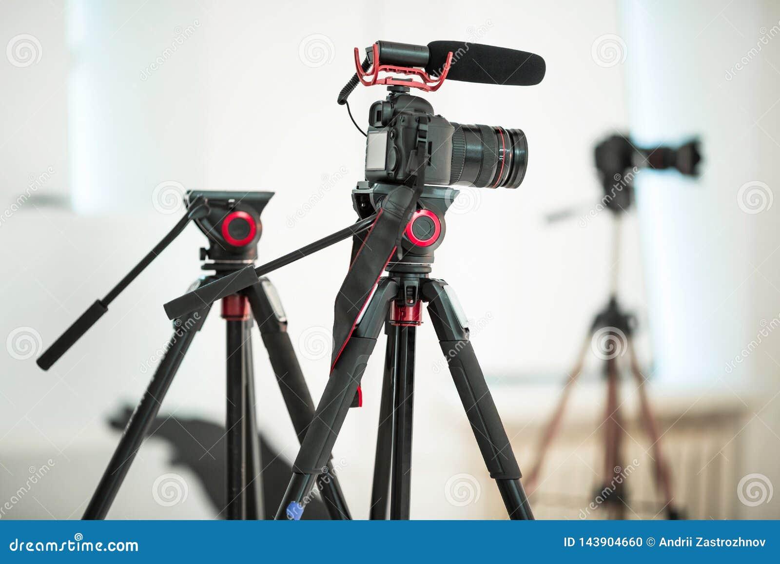 Συνέντευξη έννοιας, ψηφιακή κάμερα σε ένα τρίποδο με ένα μικρόφωνο στο στούντιο σε ένα άσπρο υπόβαθρο